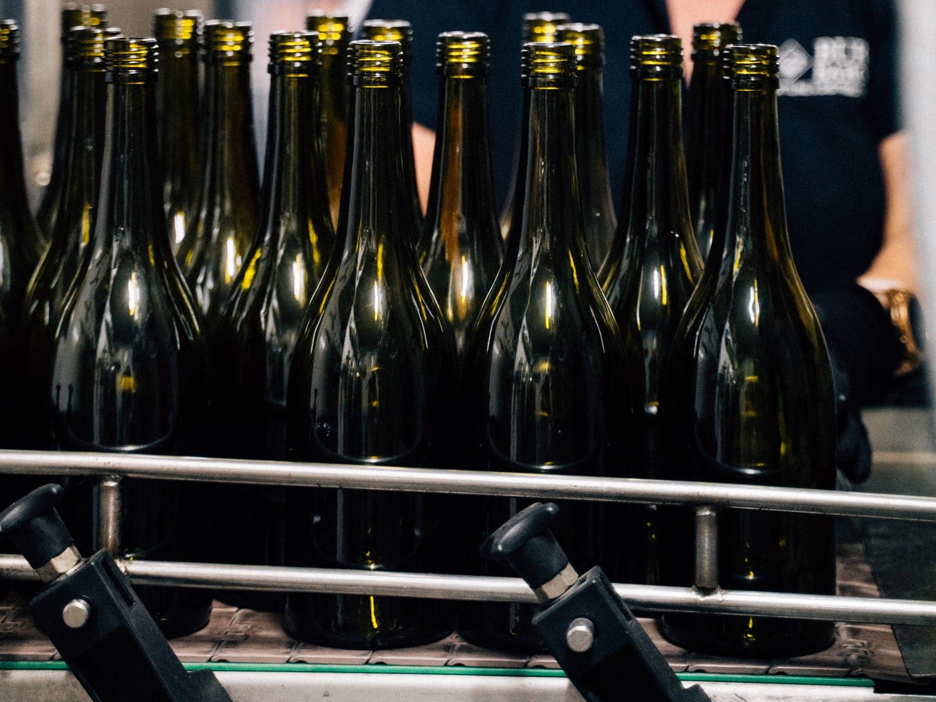 Wine bottles empty on bottling line